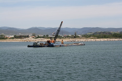 Alexandroupoli (GREECE): Digger digging sediments and up loading them to a ship